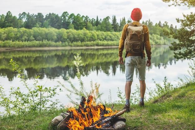 Turysta z plecakiem i czerwoną czapką spaceruje po lesie nad rzeką na tle ogniska