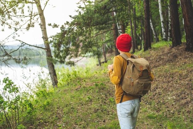 Turysta z plecakiem i czerwoną czapką spaceruje po lesie wśród drzew