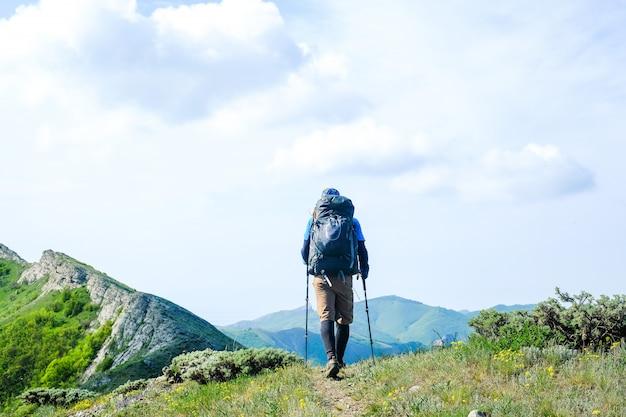 Turysta z plecakiem i kijami turystycznymi jedzie w góry