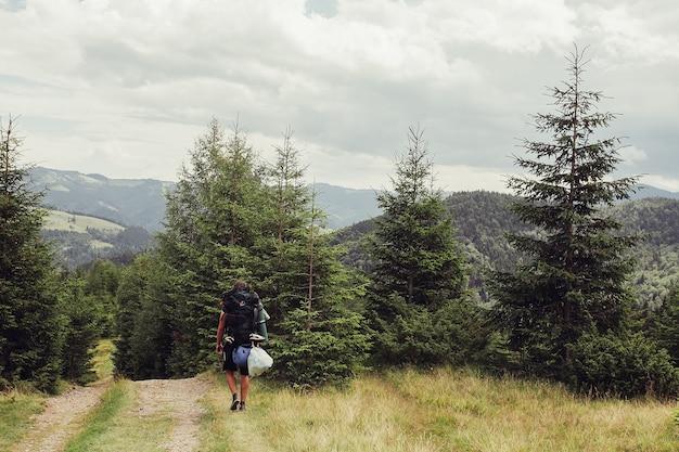 Turysta z plecakiem idzie szlakiem w kierunku górskiego grzbietu
