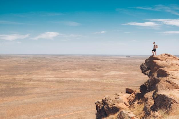 Turysta z plecakiem na szczycie góry.