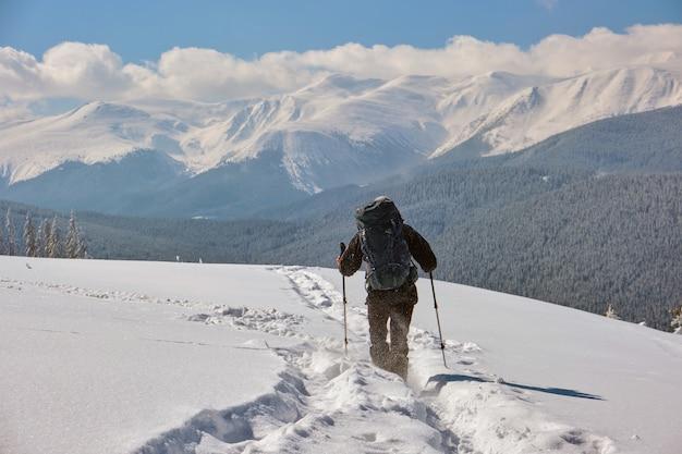 Turysta z plecakiem na zboczu góry w mroźny zimowy dzień.