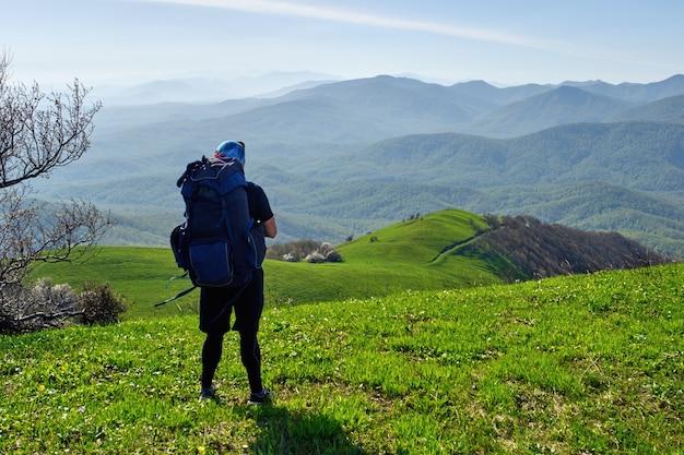 Turysta z plecakiem odpoczywa na szczycie góry i podziwia widok na dolinę