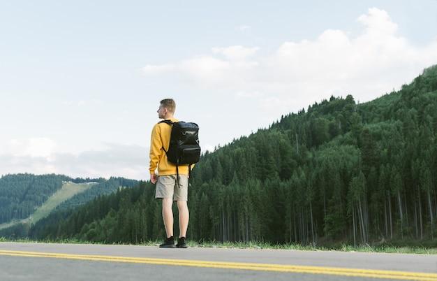 Turysta z plecakiem patrząc na lasy iglaste