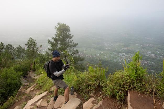 Turysta z plecakiem robi zdjęcia smartfonem w górach