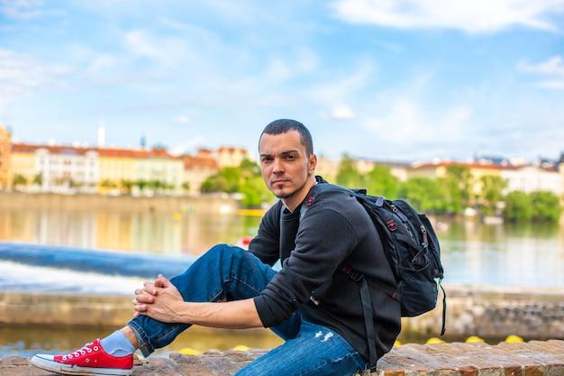 Turysta z plecakiem siedzi na skarpie w pradze z widokiem na wełtawę.
