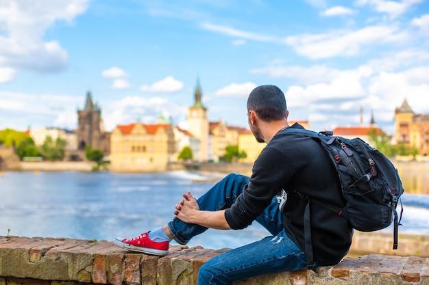 Turysta z plecakiem siedzi na skarpie w pradze z widokiem na wełtawę