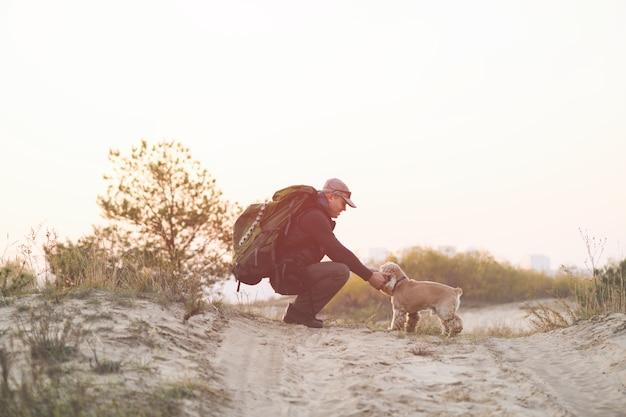 Turysta z plecakiem siedzi z psem