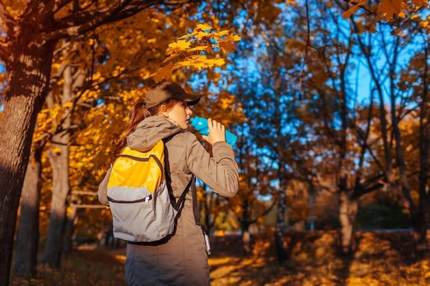 Turysta z plecakiem spacerujący w jesiennym lesie. młoda kobieta wody pitnej. podróżnik odpoczywa