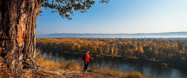 Turysta z plecakiem stoi na wzgórzu i patrzy na rzekę