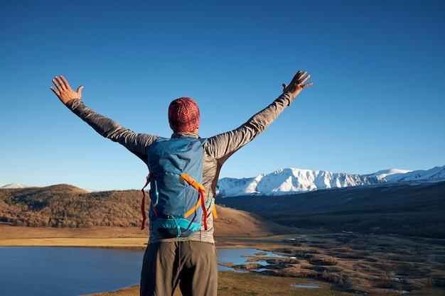 Turysta z plecakiem stojący na szczycie góry z podniesionymi rękami