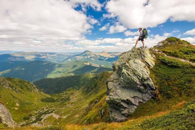 Turysta z plecakiem stojący o duży kamień w zielonej skalistej górze