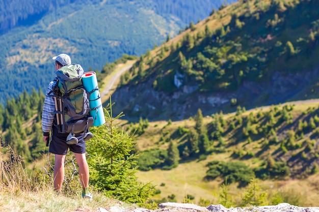 Turysta z plecakiem stojący w górach