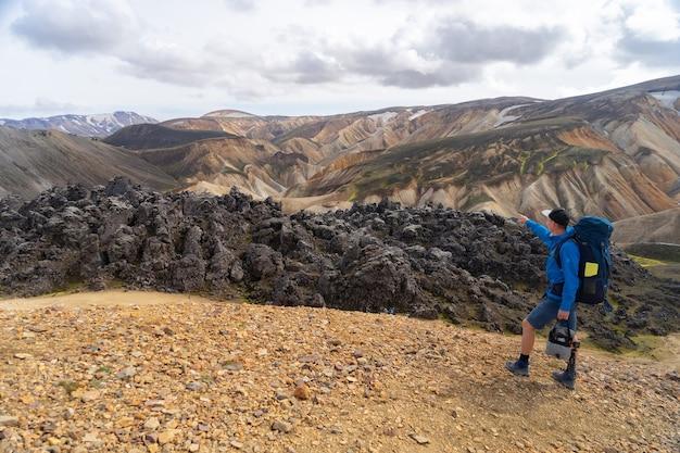 Turysta z plecakiem w dolinie landmannalaugar. islandia. kolorowe góry na szlaku turystycznym laugavegur. połączenie warstw różnokolorowych skał, minerałów, trawy i mchu.