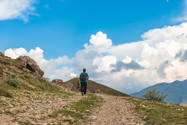 Turysta z plecakiem wspina się po górskiej drodze