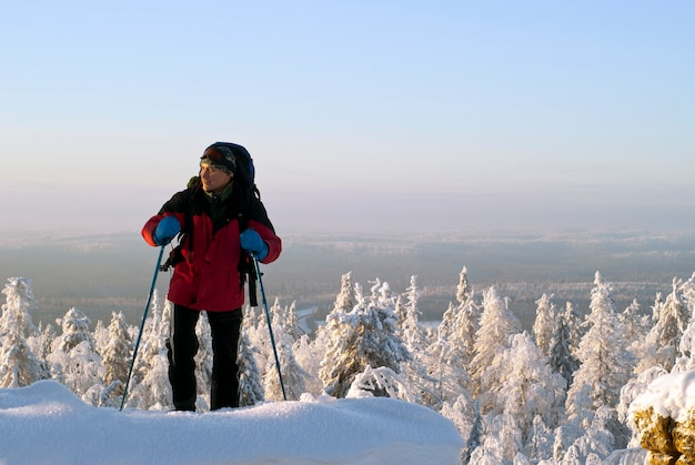 Turysta z plecakiem wznosi się na szczyt góry na tle zimowego leśnego krajobrazu