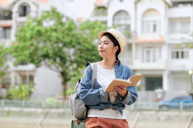 Turysta z przewodnikiem turystycznym. młoda kobieta podróżnik uśmiechnięty szczęśliwy.