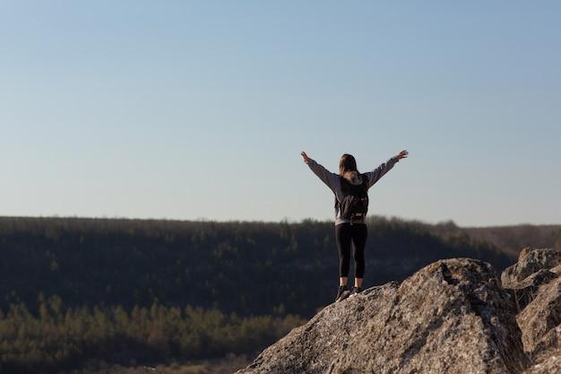 Turysta z rozpostartymi ramionami stojący na skalistej górze i cieszący się pięknym krajobrazem