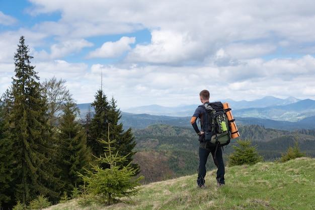 Turysta z wyposażeniem spędza czas na wędrówkach po górach