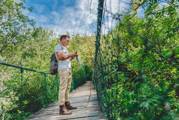 Turysta za pomocą inteligentnego telefonu na drewnianym moście zawieszenia