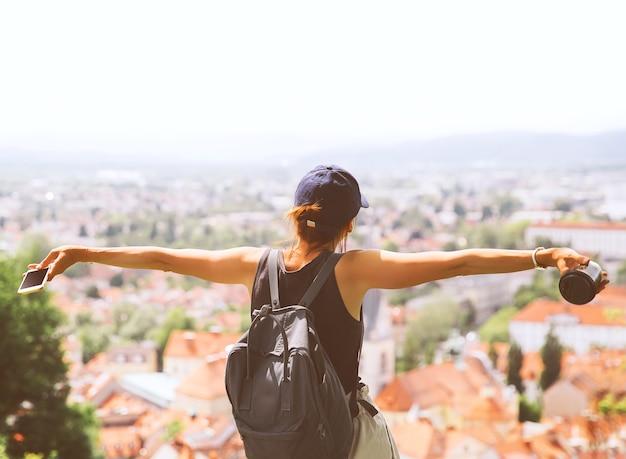 Turysta ze smartfonem i kawą w rękach na tle widok na miasto z czerwonymi dachami lublany
