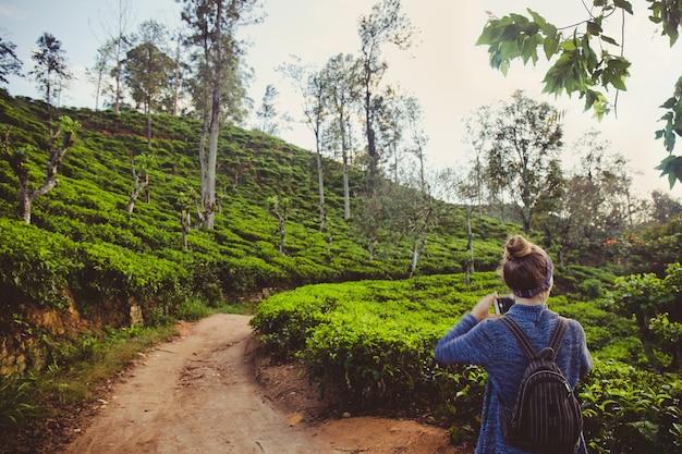 Turystka fotografująca góry i plantacje herbaty na sri lance