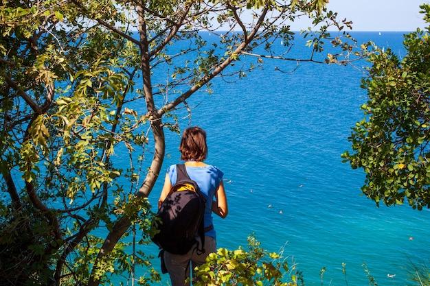 Turystka kobieta z plecakiem patrząc na morze strunjan w słowenii