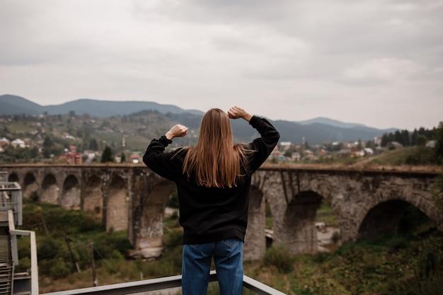 Turystka lubi podróżować do historycznych miejsc na ukrainie, wiaduktu w górskiej miejscowości wypoczynkowej worochta, karpaty. koncepcja podróży.