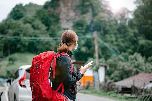 Turystka podróżująca z plecakiem, szuka lokalizacji gps na wakacje. relaks z piękną przyrodą