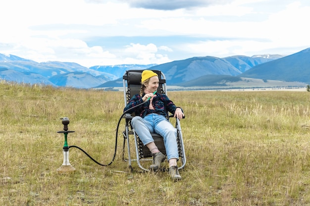 Turystka siedzi i relaksuje się w górach, paląc fajkę wodną