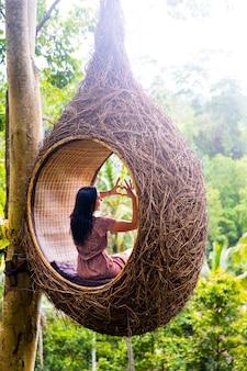 Turystka siedzi na dużym ptasim gnieździe na drzewie na wyspie bali