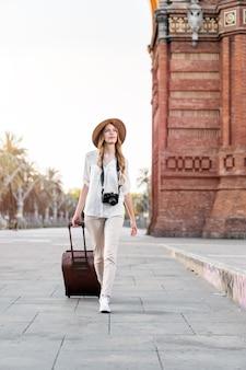 Turystka spacerująca po mieście z walizką i starodawnym aparatem.