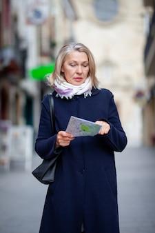 Turystka spaceruje ulicami miasteczka z mapą w ręku.