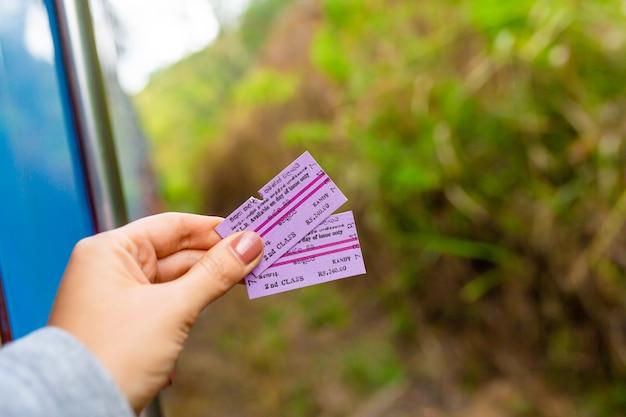 Turystka trzyma w ręku bilet na pociąg na sri lance. podróżowanie po sri lance pociągiem. kolombo, sri lanka - 02.03.2018