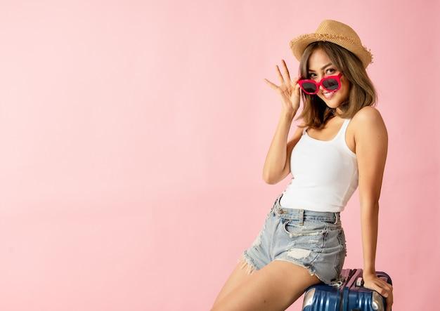 Turystka ubrana w letnią sukienkę i okulary przeciwsłoneczne usiadła na bagażu zaskoczyła ją promocją