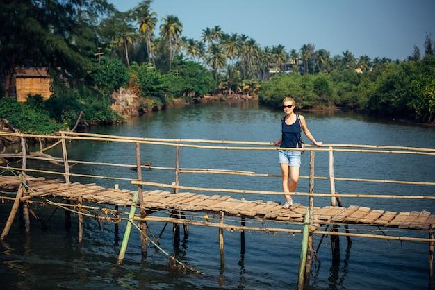 Turystka w dżinsowych szortach z krótką fryzurą w słoneczny tropikalny dzień. młoda ładna dziewczyna stoi na drewnianym moście nad małą rzeką przeciw palmowej dżungli i niebieskiemu niebu.