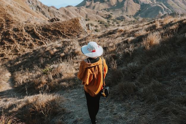 Turystka w letnim kapeluszu schodząca sama ze wzgórza na wyspie padar