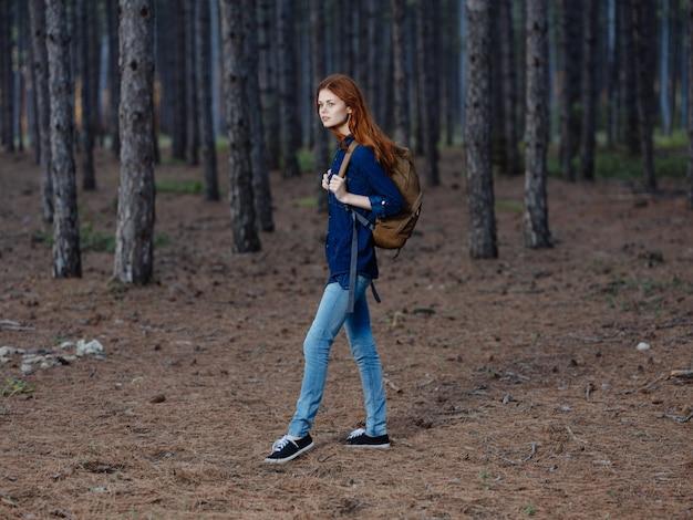 Turystka w pełni wzrostu w sosnowym lesie z plecakiem na plecach