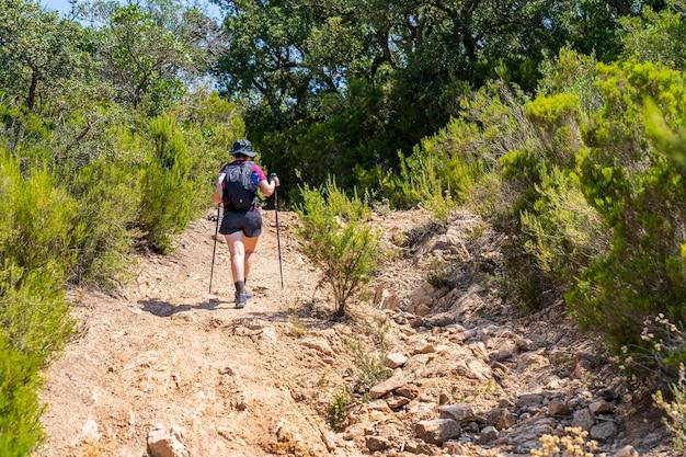 """Turystka wspinająca się ścieżką przez """"massis de les cadiretes""""."""