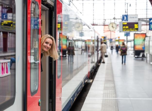 Turystka wygląda z pociągu na peronie kolejowym, podróżuje po europie. transport europejskimi kolejami, komfortowa turystyka