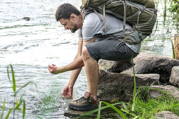 Turystka z dużym plecakiem turystycznym nad górską rzeką w letnim upale.