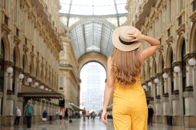 Turystka z mody przestaje wyglądać na oczarowaną galerię vittorio emanuele w mediolanie we włoszech. dziewczyna z podróży lubi odwiedzać centrum mediolanu, słynne miejsce dla turystyki i mody.