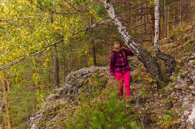 Turystka z plecakiem ostrożnie pokonuje górski szlak wśród jesiennego lasu