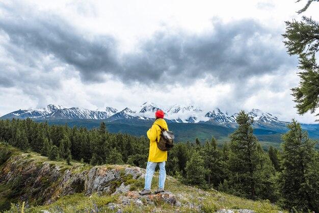 Turystka z plecakiem patrzy na krajobraz gór