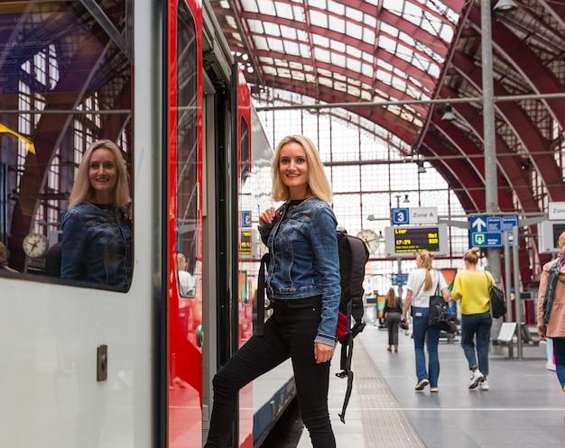 Turystka z plecakiem wchodzi do pociągu na peronie, podróżuje po europie. transport europejskimi kolejami, komfortowa turystyka i podróżowanie