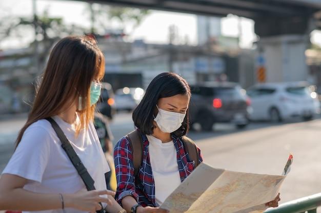 Turystki dziewczyny w maskach na twarz przy ulicy. kobiety podróżują podczas kwarantanny koronawirusa.