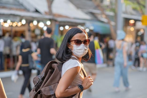 Turystki dziewczyny w maskach na twarz przy ulicy.