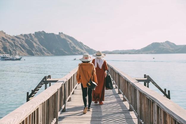 Turystki spacerujące po drewnianym molo otoczonym morzem