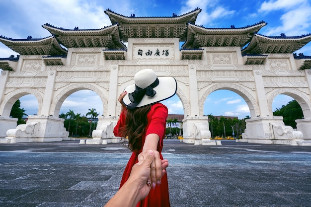 Turystki trzymające mężczyznę za rękę i prowadzące go do izby pamięci czang kaj-szeka w tajpej na tajwanie.