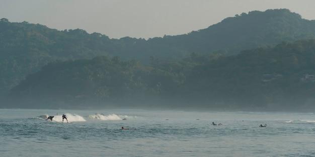 Turystów korzystających z surfingu w morzu, sayulita, nayarit, meksyk